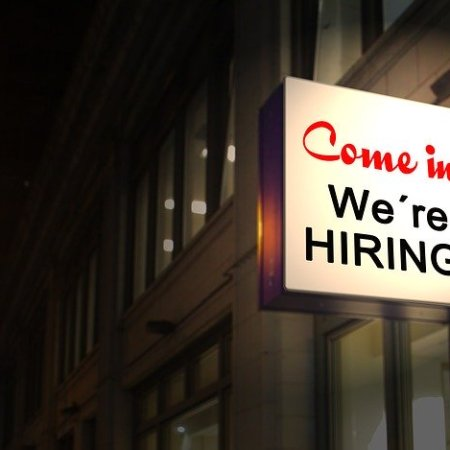 We're hiring sign for new jobs on a darkened alley