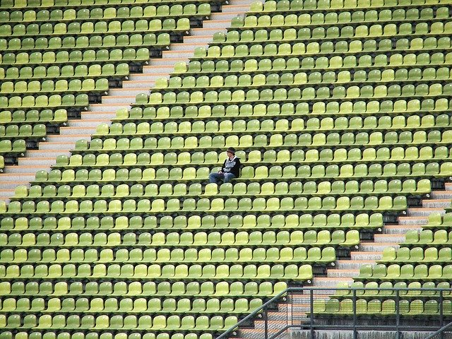 Olympic stadium with only one man sitting down on the seats