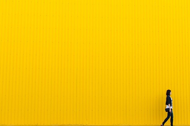 A yellow wall with a lady walking past it