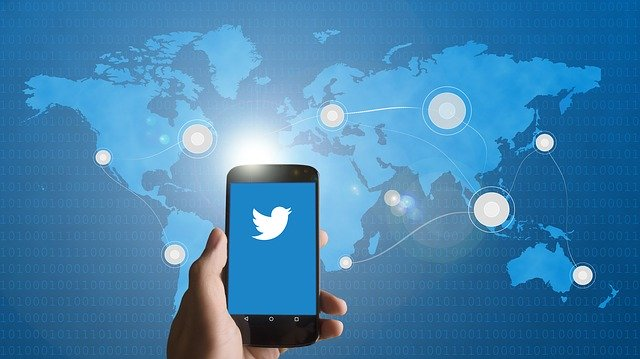 A smartphone with the Twitter icon and the world map behind it