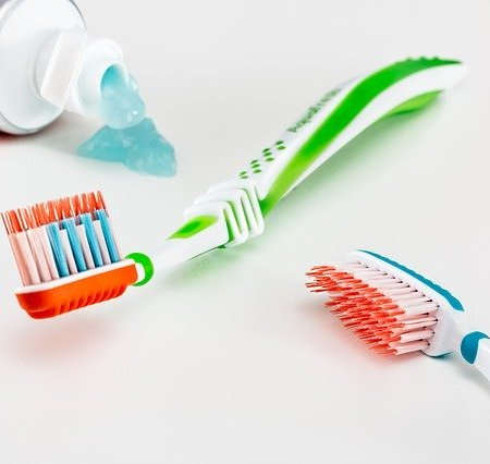 Toothbrushes lying next to a leaking tube of toothpaste