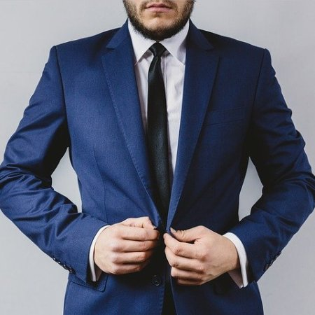 A gentleman putting on a blue suit