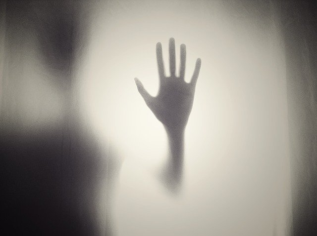 A scary hand on a pane of glass