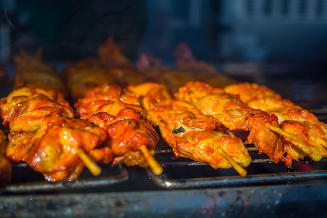 A chicken kebab on a grill cooking