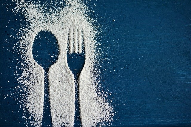 Outline of a spoon and fork in sugar dusting