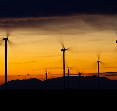 Wind turbines in a sunset creating gusts