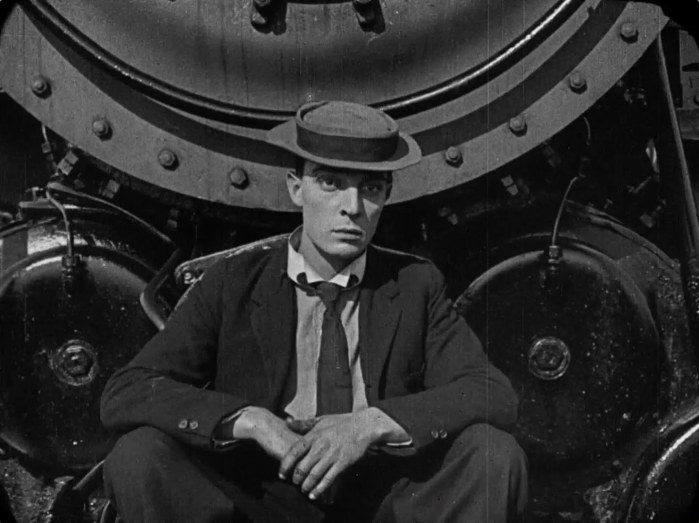 Buster Keaton sitting down looking deadpan
