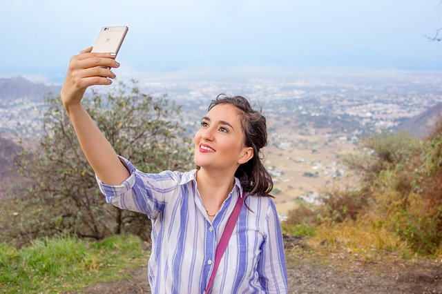 A woman taking a selfie with scenery in the background