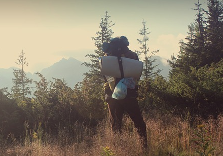 Man with a sleeping bag in nature