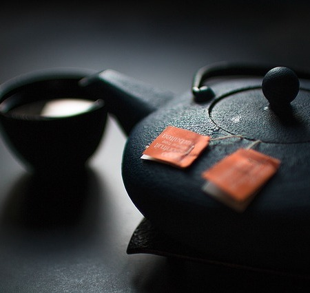 Teapot with some tea stewing and a cup