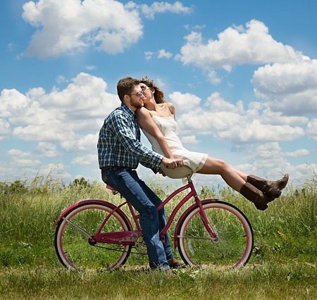 Good looking happy young couple cycling in a field