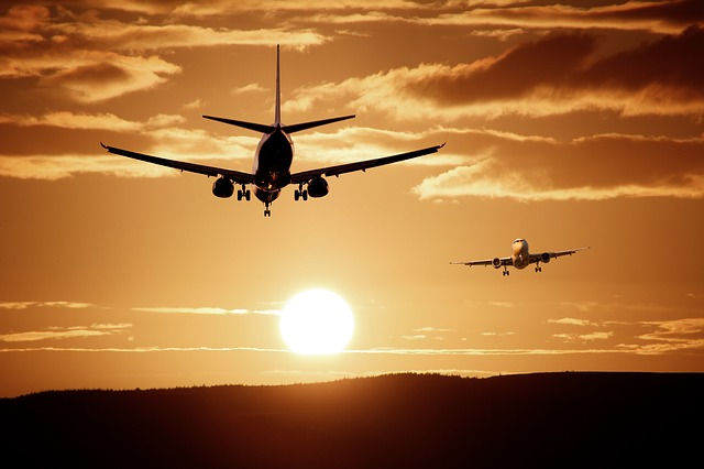 Two aeroplanes flying in a sunset