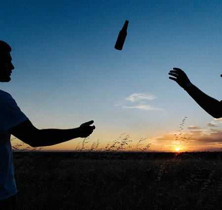 Men exchanging a beer during a sunset.