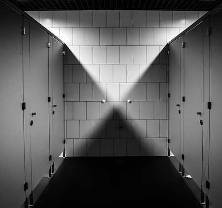 Toilet cubicles in a black and white bathroom
