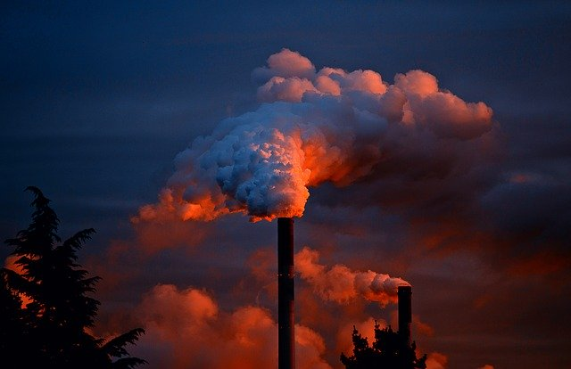 Pollution coming out of a chimney during a sunset