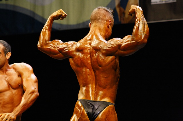 A greased up, tanned, male bodybuilder wearing a thong