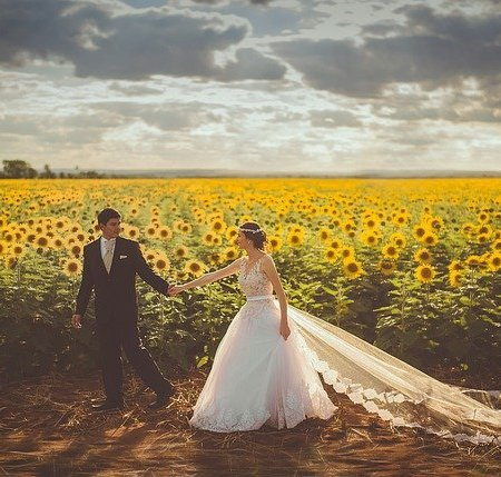 A bride and groom walking in a field of sunflowers
