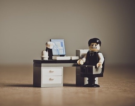 A LEGO employee looking unhappy in the workplace