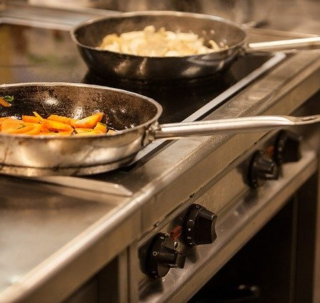 Frying pans in a kitchen cooking food