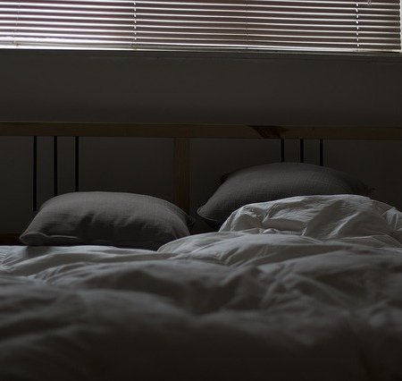 An unmade bed in the dark