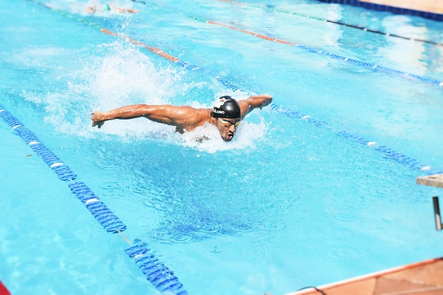 A man performing the butterfly swimming stroke in a pool