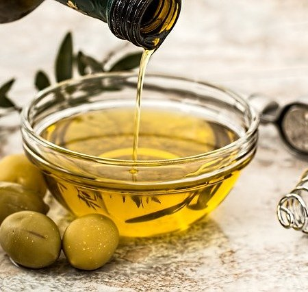 Olive oil being poured into a glass cup