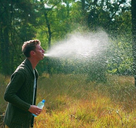 A man spitting out a lot of water in the countryside