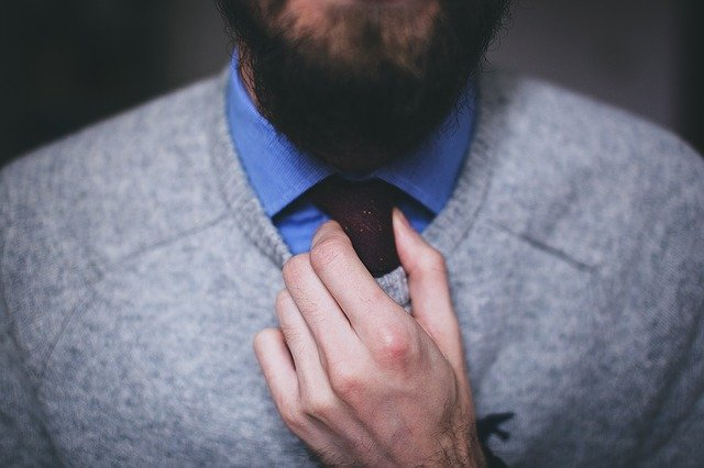 A bearded man adjusting his tie