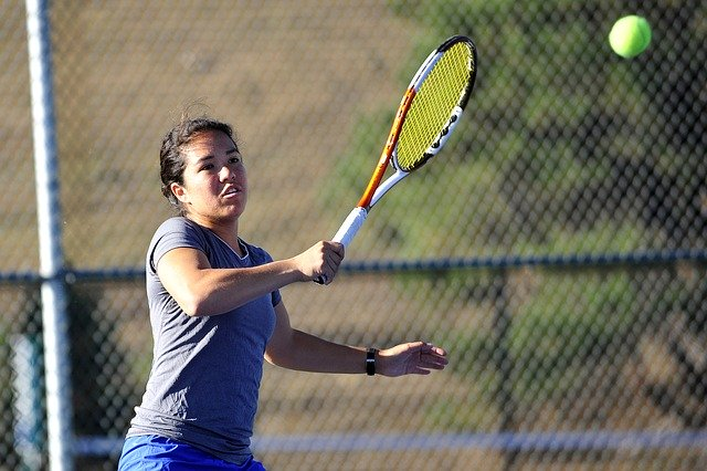 A female tennis playing hitting a ball