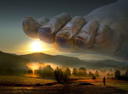 A giant foot with toenails about to stamp on idyllic countryside