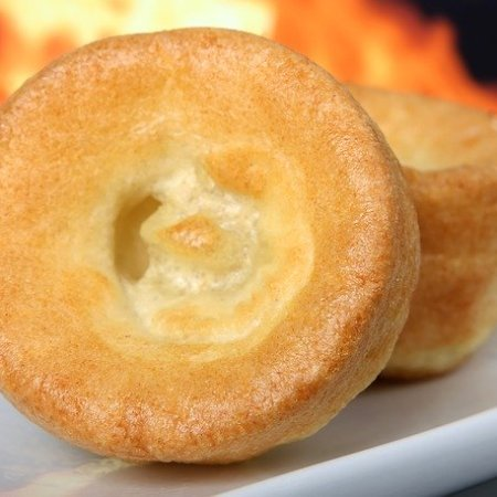 Two Yorkshire puddings with fire in the background