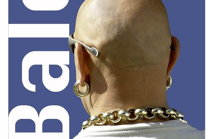 A bald man with a gold chain around his neck.