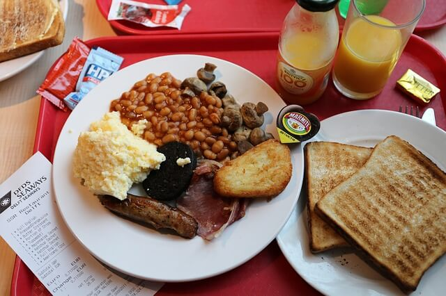 A full English breakfast with baked beans, toast, a sausage, hash brown, and mash.