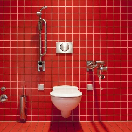 A toilet with a red tiled background