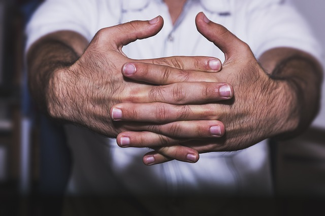 A man holding his knuckles out to crack them