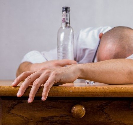 A man slumped at a bar hungover with a bottle of alcohol