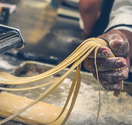 A man holding strings of fresh pasta.