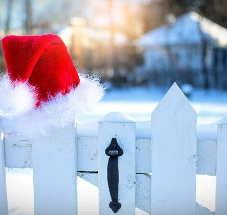 A Santa hat on a picket fence line in the snow.