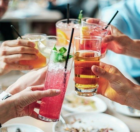 A crowd of friends clinking alcoholc beverages