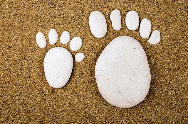 Human feet made out in the shape of rocks on a sandy beach