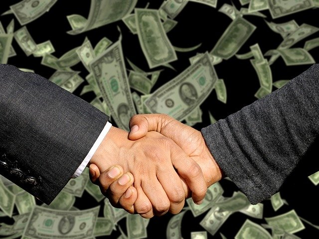 Two businessmen shaking hands to the backdrop of money.