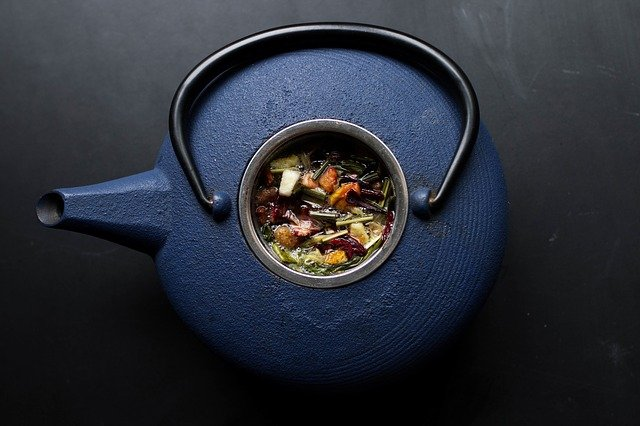 A blue teapot with herbal tea in its centre