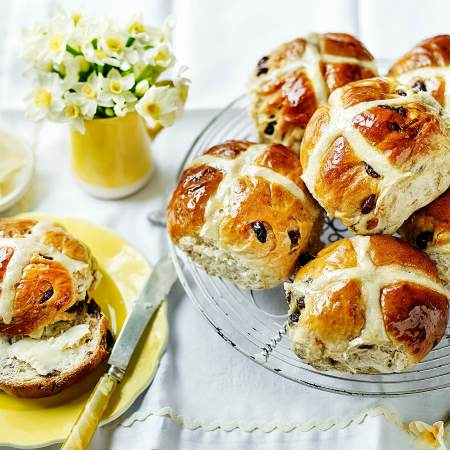 A selection of hot cross buns, one of which is on a yellow plate.