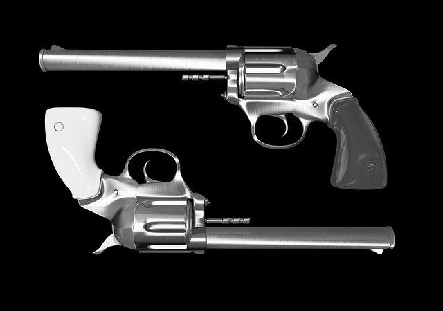 Two guns placed side by side with a black background