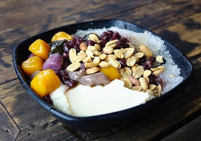 A bowl of curd with fruit and nuts