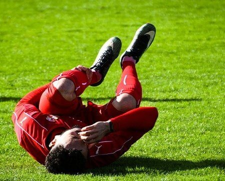 A footballer rolling on the pitch in pain clutching his kneecap