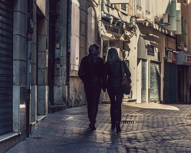 A couple walking on a cobbled street holding hands