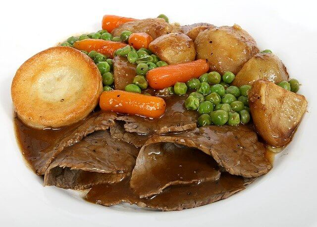 A roast dinner with beef, gravy, roast potatoes, veg, and a Yorkshire pudding