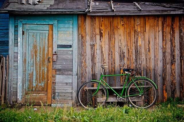 A run down shed with a green bike next to it