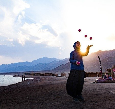 A woman juggling four balls in a mountainous region